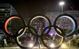 People take photographs in front of the Olympic rings.