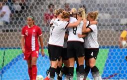 Sara Dabritz is congratulated by team mates after kicking a goal.