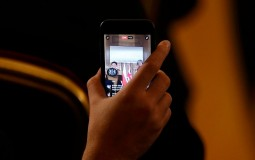 A journalist uses their phone to report live to social media